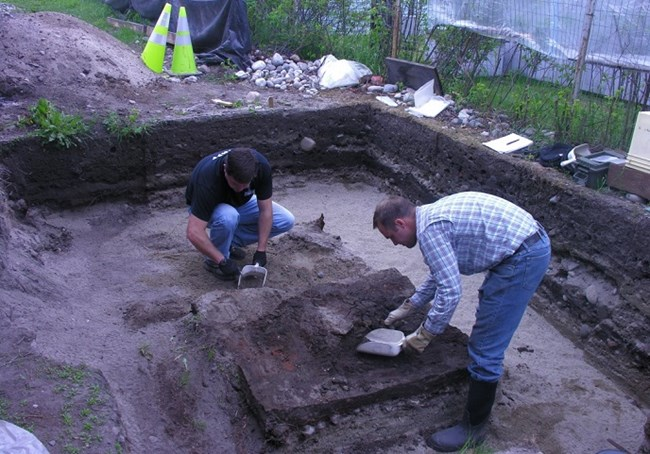 Two people working with tools in an square hole