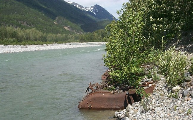 Large rusted metal embedded at edge of river