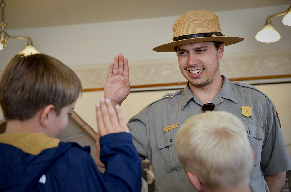 A ranger faces two boys with right hands raised.