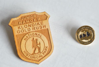 "Wooden badge with text ""Junior Ranger Klondike Gold Rush National Historical Park"" and metal pin with text ""Klondike Gold Rush NHP Skagway & Seattle"""