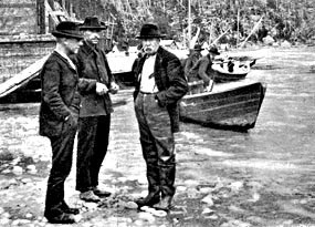 Black and white photo of three men standing at the edge of water with boats behind them.