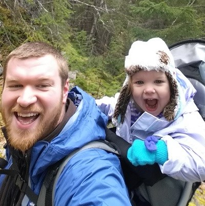 Man on trail with child in in back pack carrier