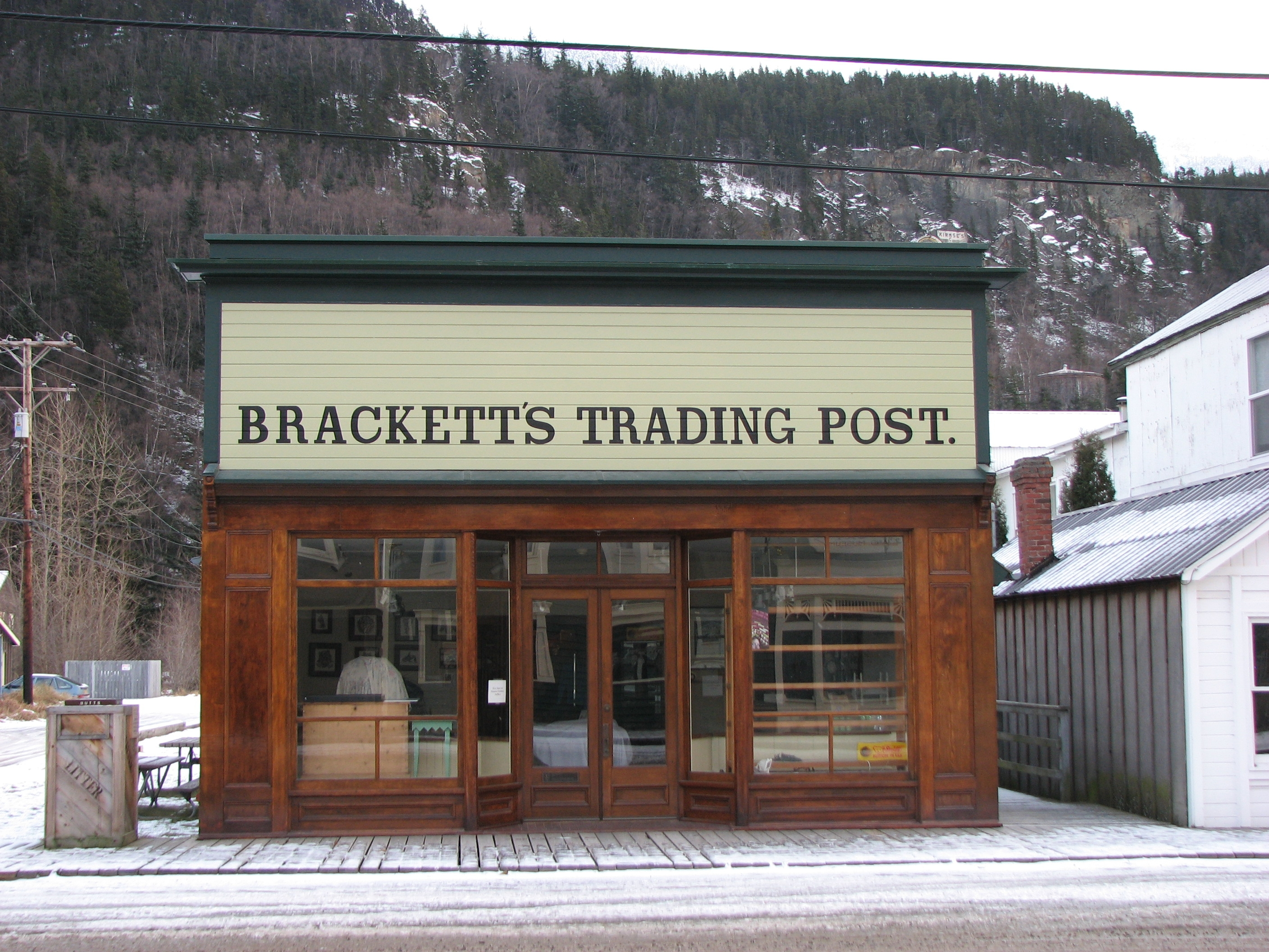 wood one story building with large painted sign covering top front of entire structure. Sign says Brackett Trading Post