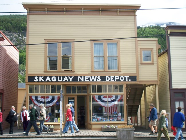 "Two story Victorian style building with sign reading ""Skaguay News Depot."""
