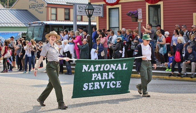 "Two people carrying ""National Park Service"" banner on a crowded street"