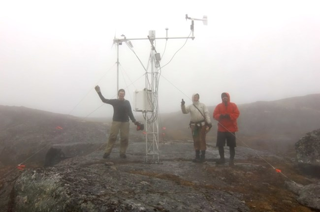 Three people stand on a rocky area in the fog next to a metal tower