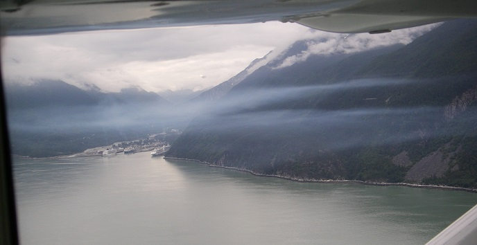 Layer of blue smog over water and town viewed from an airplane