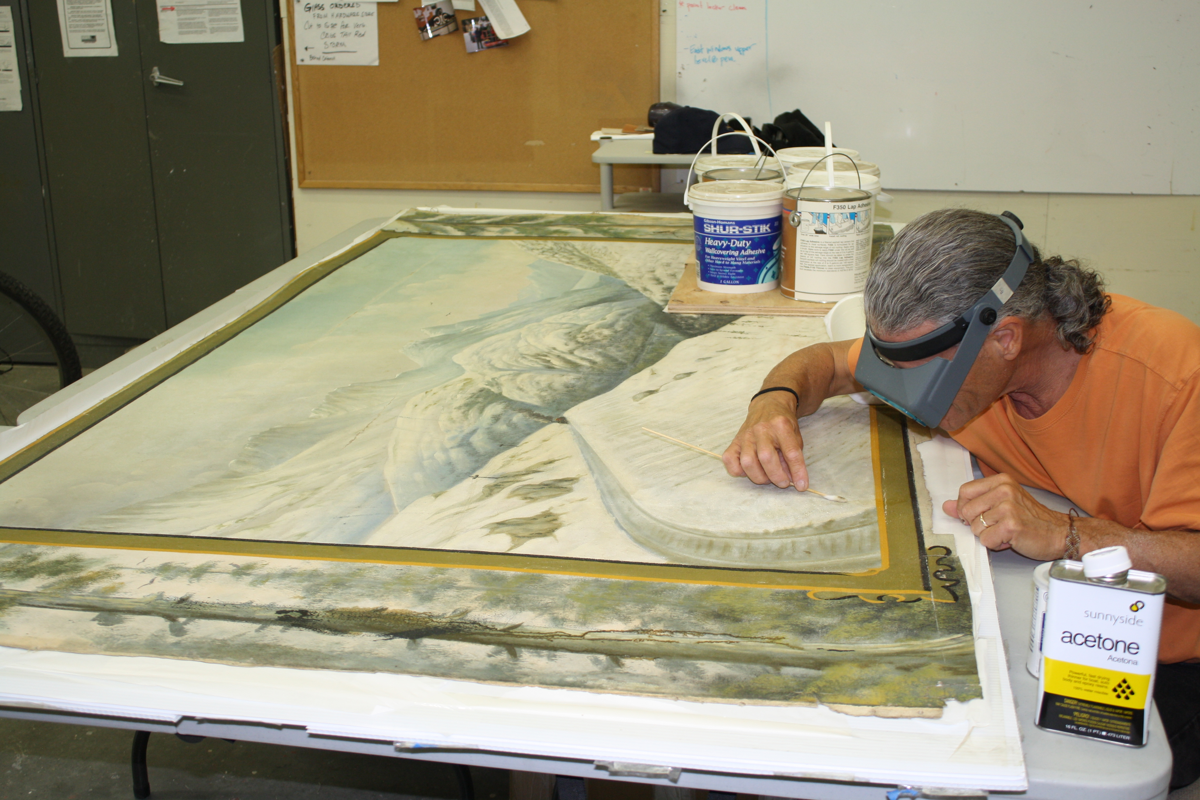 A man works on a painting with cleaning tools.