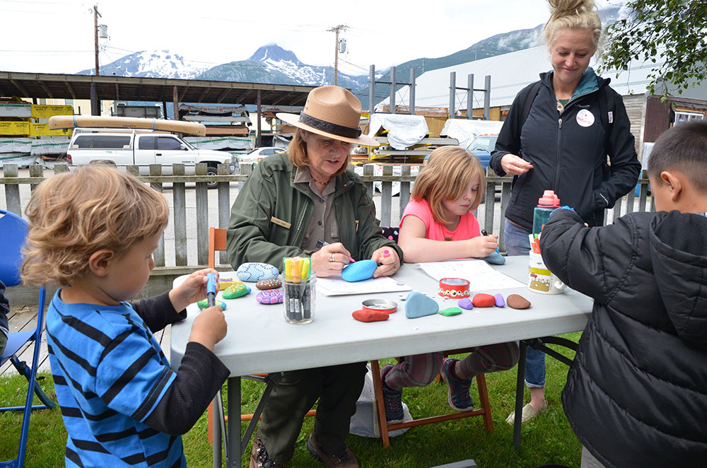 a ranger paints rocks with kids
