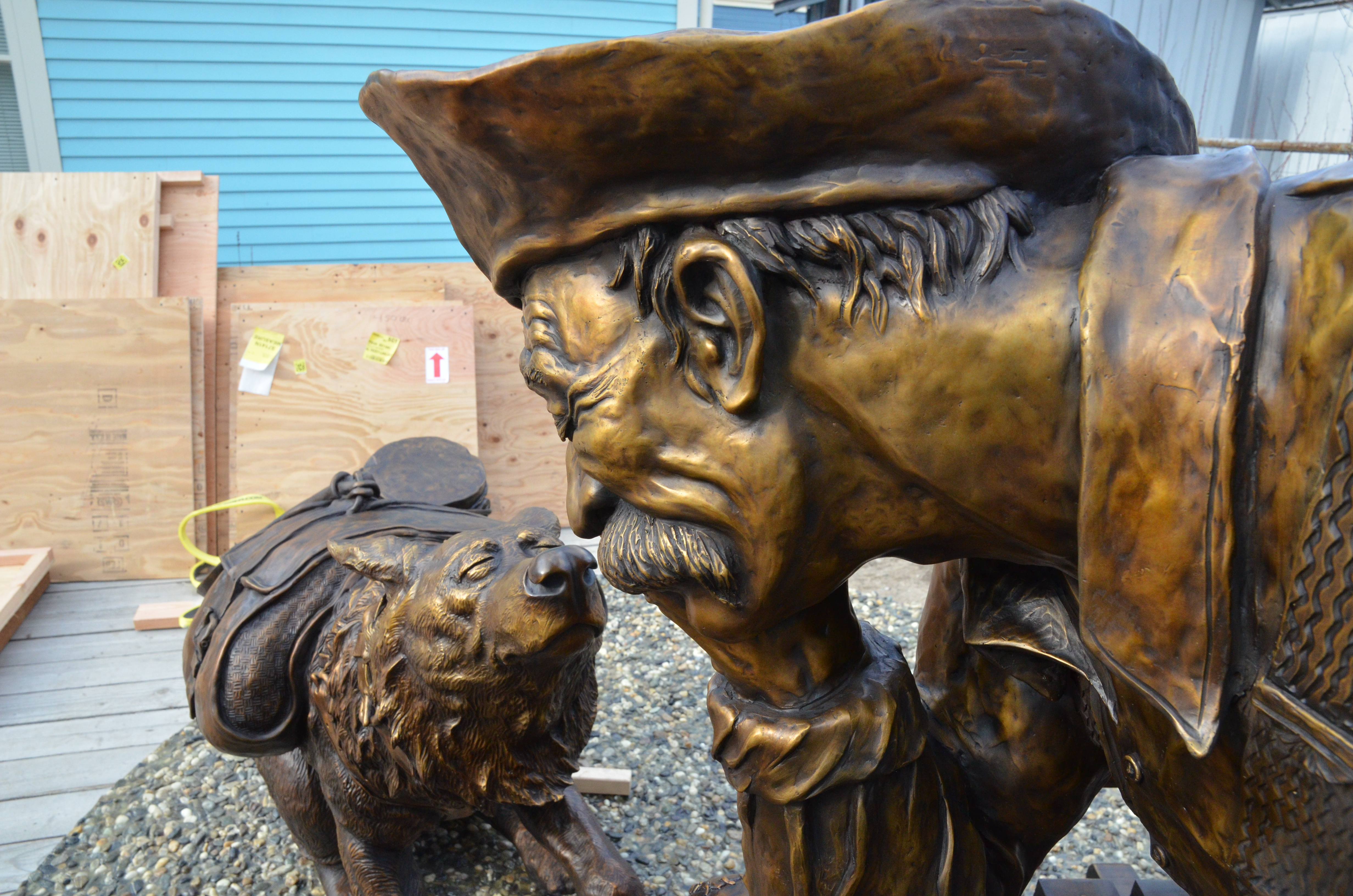 Close photo of bronzed sculpture of a man and a dog