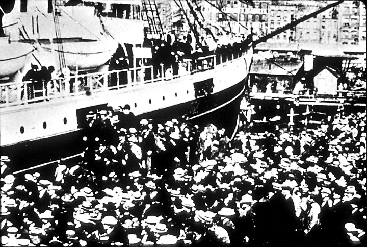 Crowd tries to board sailing vessel in 1897.  Black and white image.