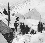 Black and white photo of people standing in snow near canvas tents.