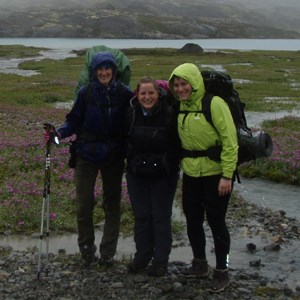 Three hikers stand in the rain near a stream