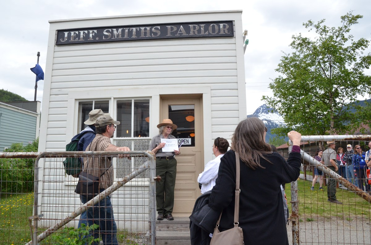 "Facing the camera, a ranger stands on the steps of a small building with a sign ""Jeff. Smiths Parlor"" while people face her"