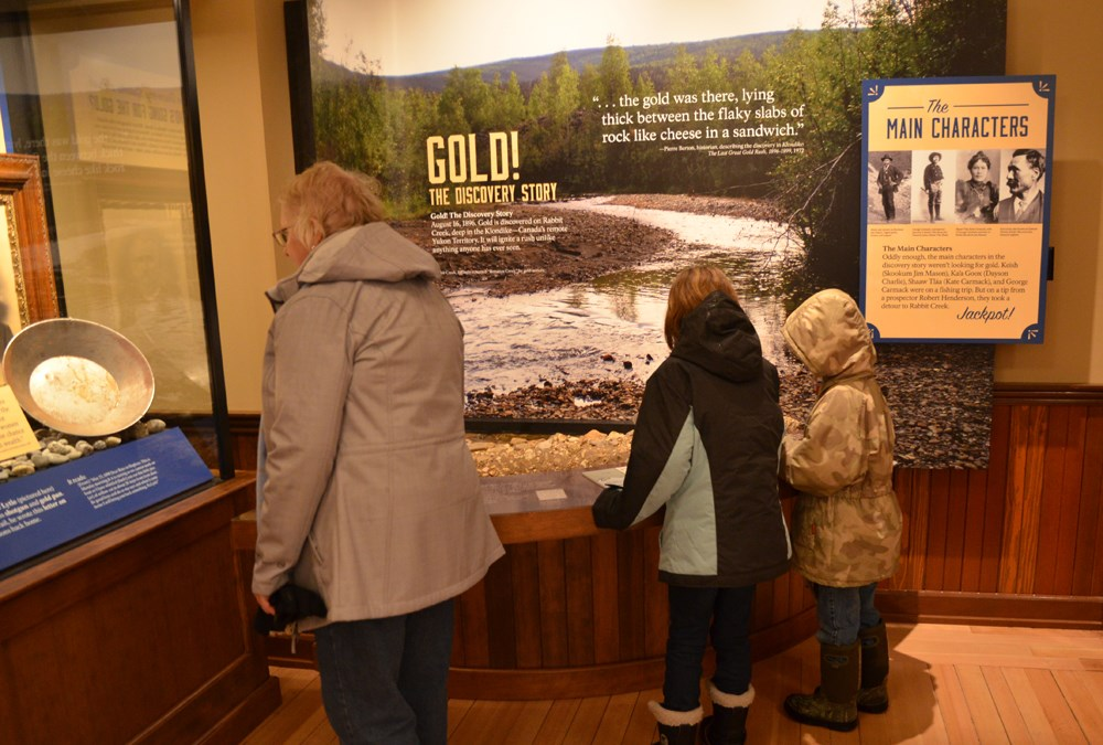 An adult and two children look at museum exhibits.