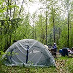 A tent in a forested area with people in the background