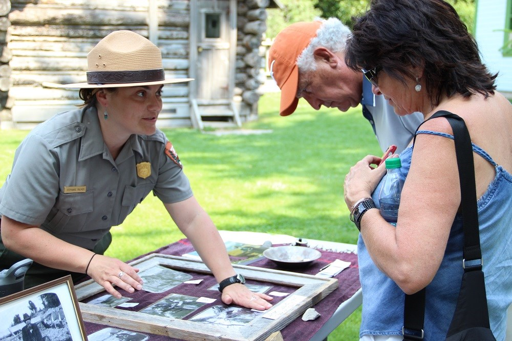 Park Ranger talks to visitors at an outdoor table