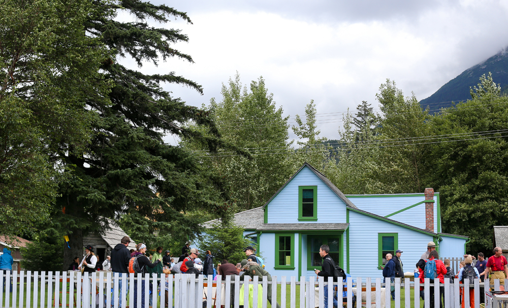 Crowd of people in the yard in front of a bright blue house
