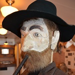 Close up of manikin face with hat, beard, and cigar