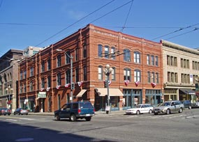 large, brick three story building on busy corner in Pioneer Square, Seattle