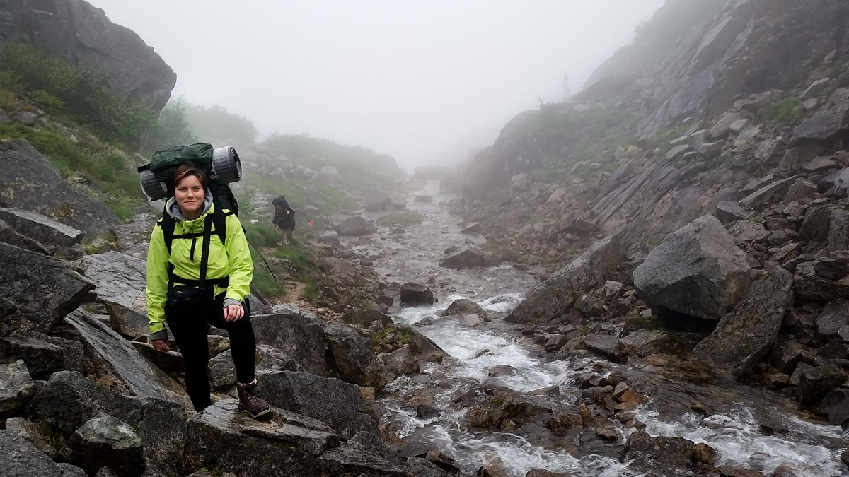 A backpacker poses along a rocky creek in the fog
