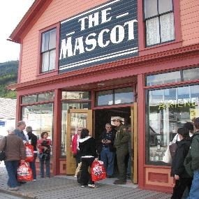 Modern photo of The Mascot saloon museum with ranger talking to visitors