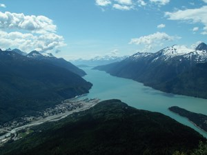 View of townsite and fjord surrounded by mountains from a mountain.