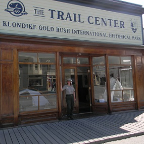 "Building with large windows and sign reading ""The Trail Center"" with a ranger in front."