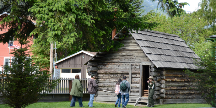 People stand with a ranger in front of a log cabin.