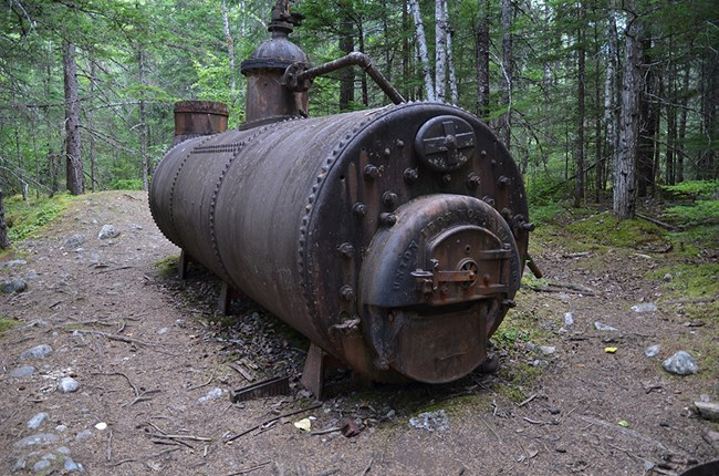 A large, rusty boiler sits in a forest clearing