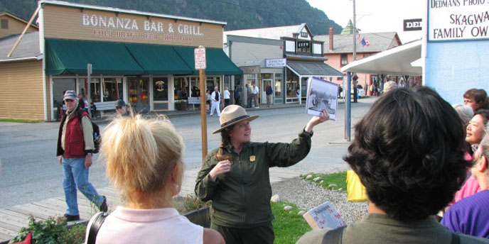 A ranger shows historic photos on a town tour