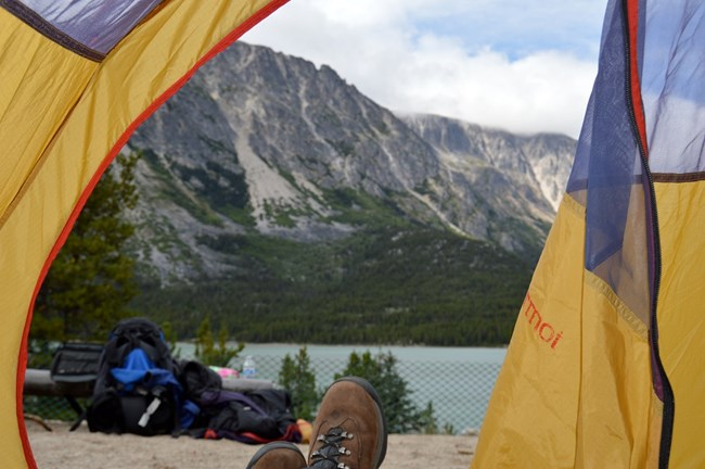 Looking out of a tent toward mountains and a lake