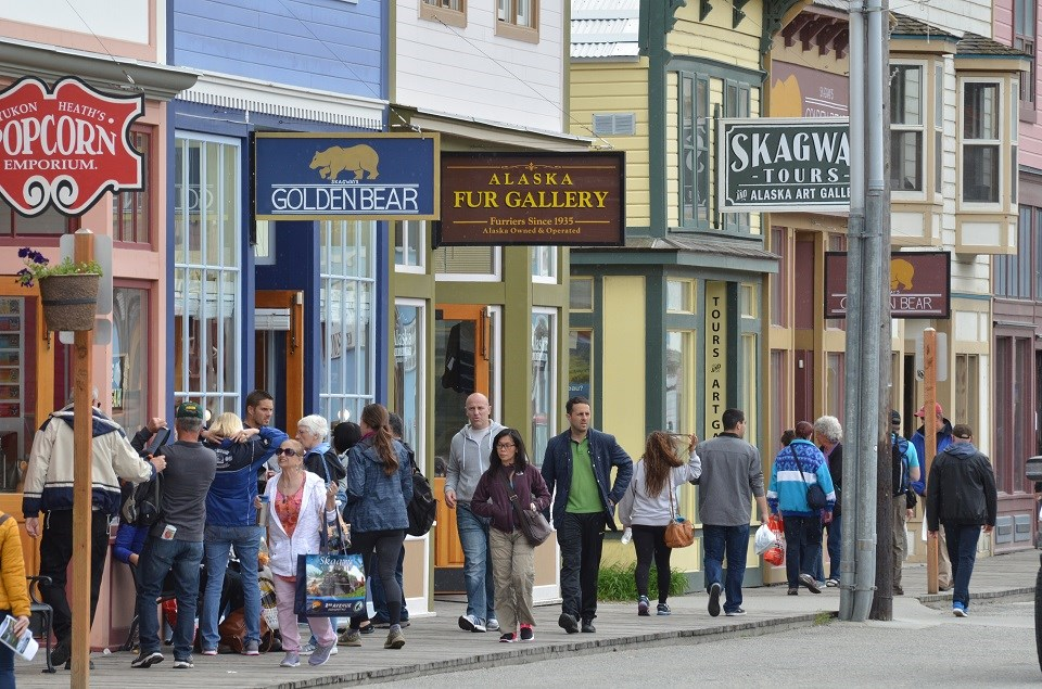 A crowd of visitors walks on wooden boardwalks in front of gold rush era buildings that are now modern stores
