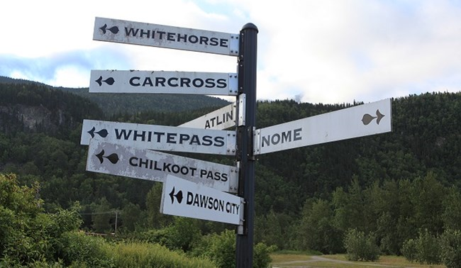 Multiple signs on a pole point in the directions of gold rush destinations