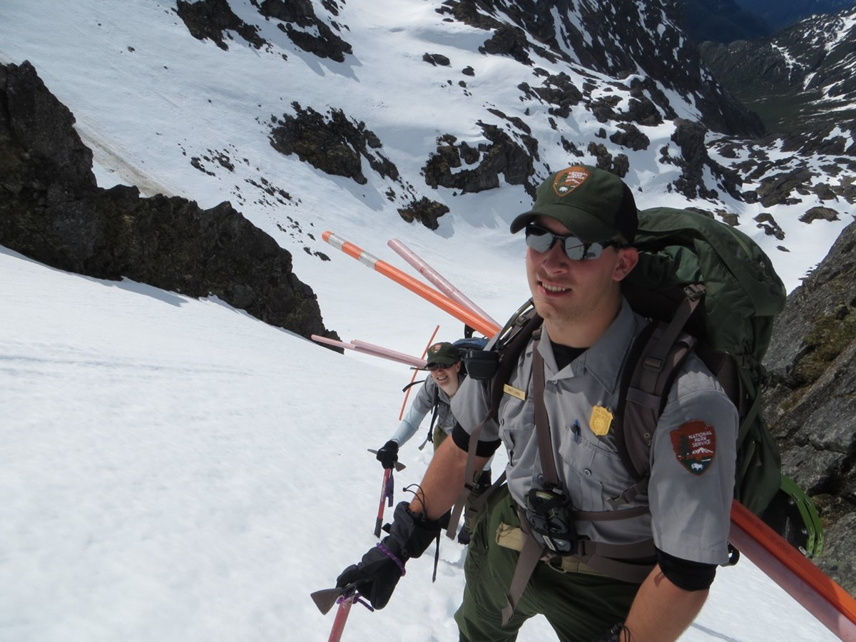 Two rangers carry trail markers up a steep, snowy mountain