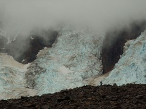 A person stands on rocky ground in front of a cascade of glacier ice