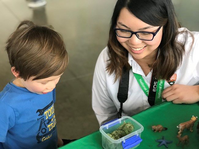 A volunteer and a child examine moss on a table