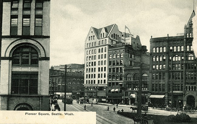"A black and white view of city buildings with a busy street in the middle. Text reads ""Pioneer Square Seattle, Wash."""