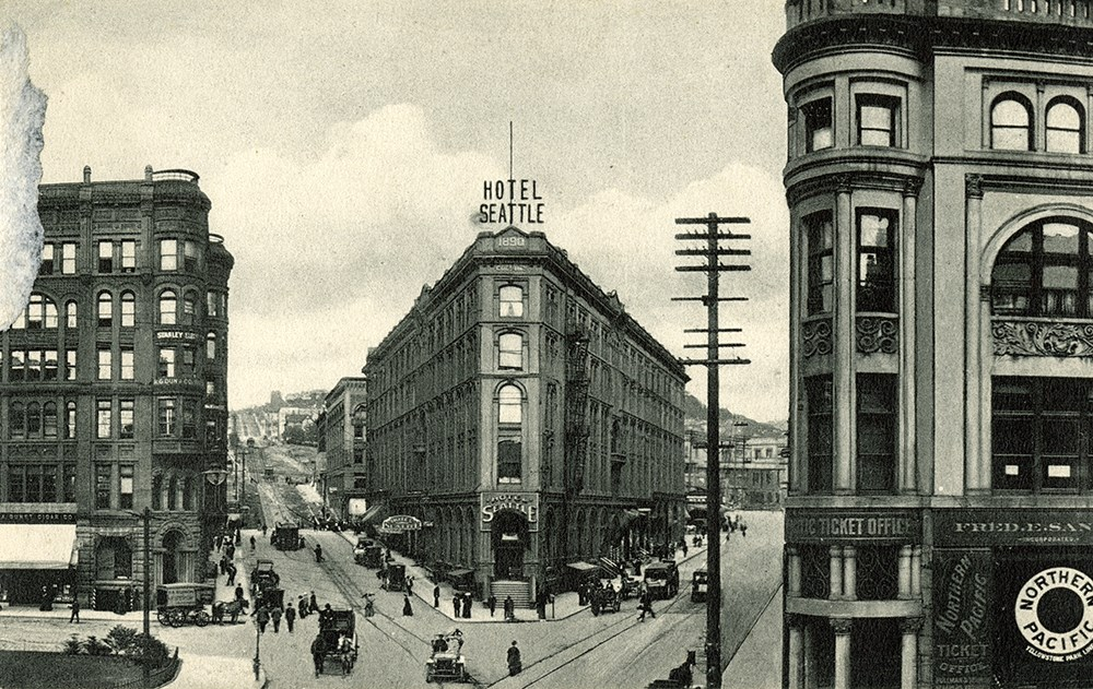 A black and white postcard image of a triangle shaped building between two streets.
