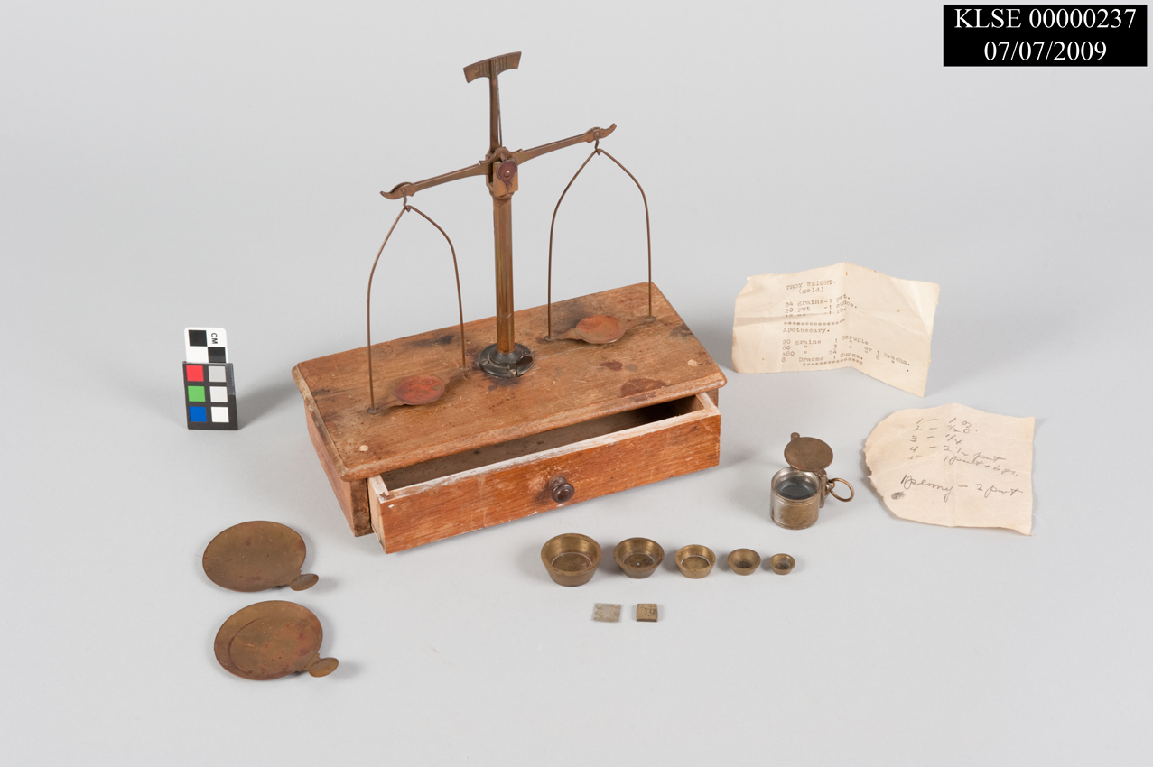 "Artifact photo showing gold scales, metal pieces, paper labels, and color card with text ""KLSE 0000237 07/07/2009"""