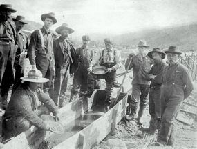 Historic image of men gathered around a sluice box