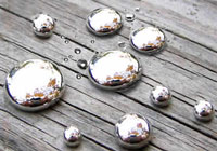 Nine reflective silver bubbles sit on a piece of wood.