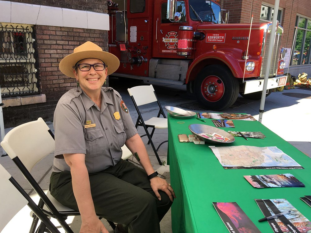A ranger sits at a table looking at the camera.  A firetruck is in the background