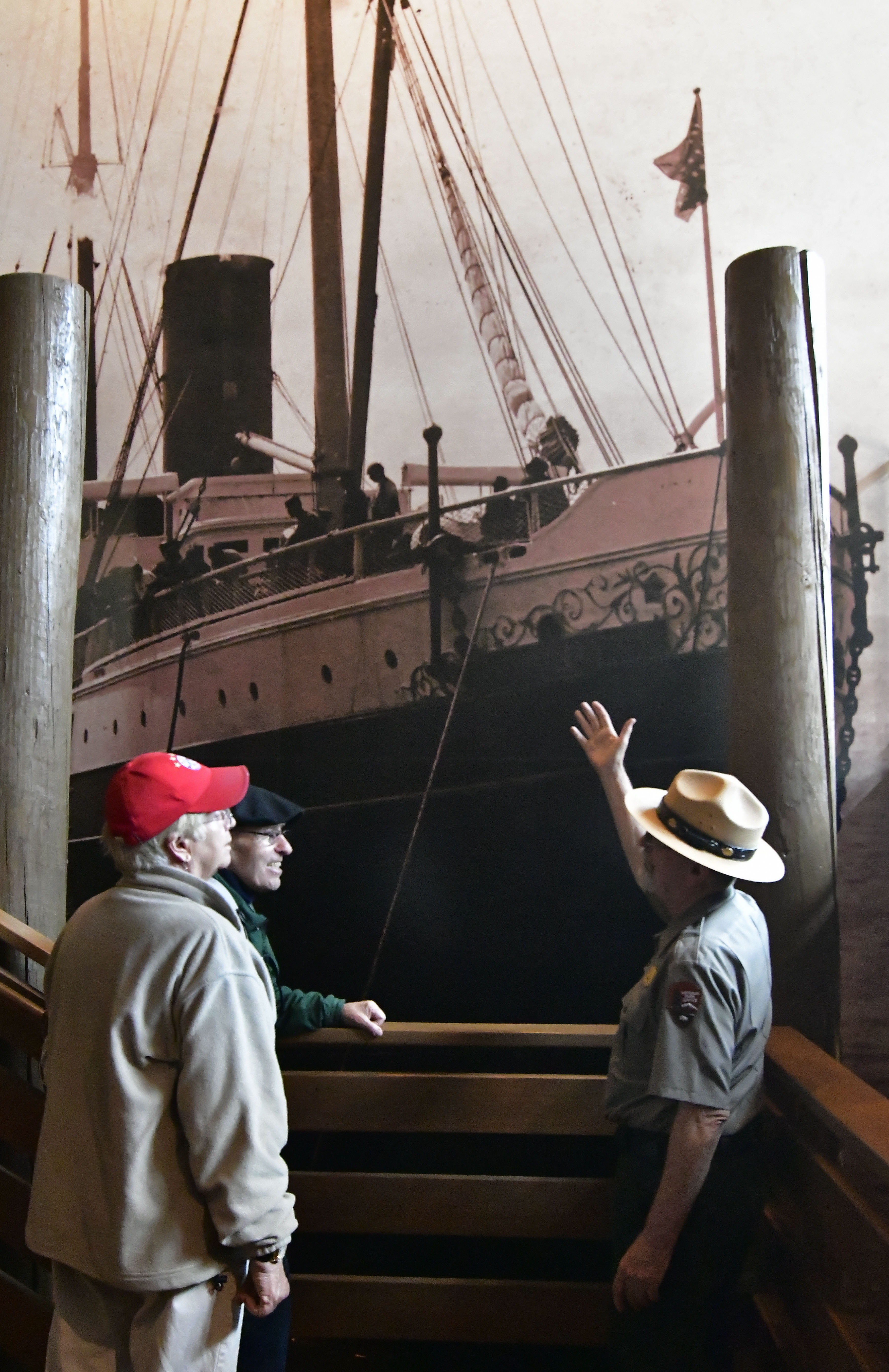 Ranger discussing large photo mural of a period steamship