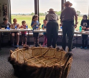 6 kids sit at tables inside working on craft. 2 rangers stand and support them. Large bull boat in foreground.