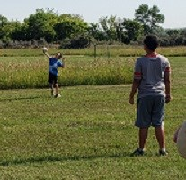 2 boys face each other on the grass. 1 throws a ball using a Y-shaped stick.