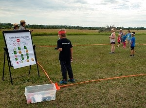 7 kids stand on grass within an orange square boundary. 2 rangers stand behind a Native Prairie Tag Rules poster.