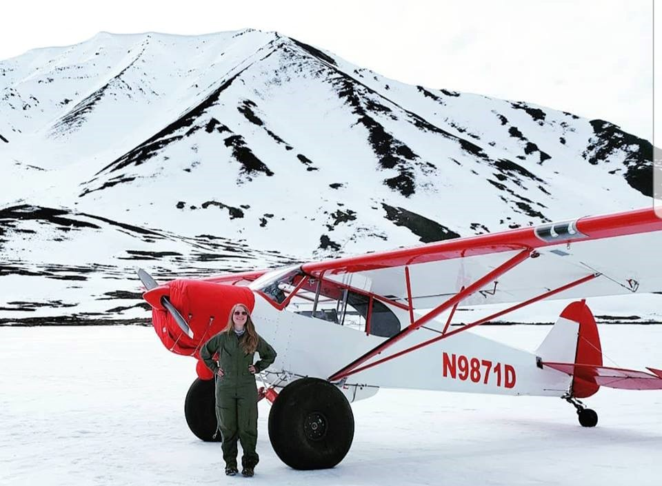 Observer Sara Germain poses for a photo in front of one of the Supercubs used on the aerial survey. Photo by NPS/Max Newton.