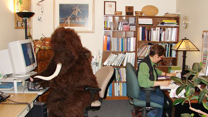 Woman and person in a mammoth costume working in an office