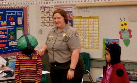 Park ranger in classroom with two students in insect costumes